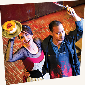 A woman holding a meat pie over her head next to a man holding a bloody knife over his head
