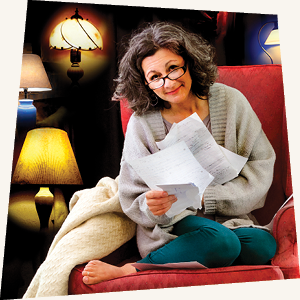 Tiny Beautiful Things image - a woman sitting in a chair holding papers with lamps behind her