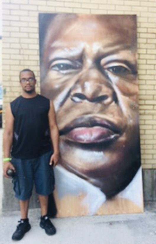 A black man standing in front of a large painting of Rep John Lewis in spray paint, propped up against a tan brick wall